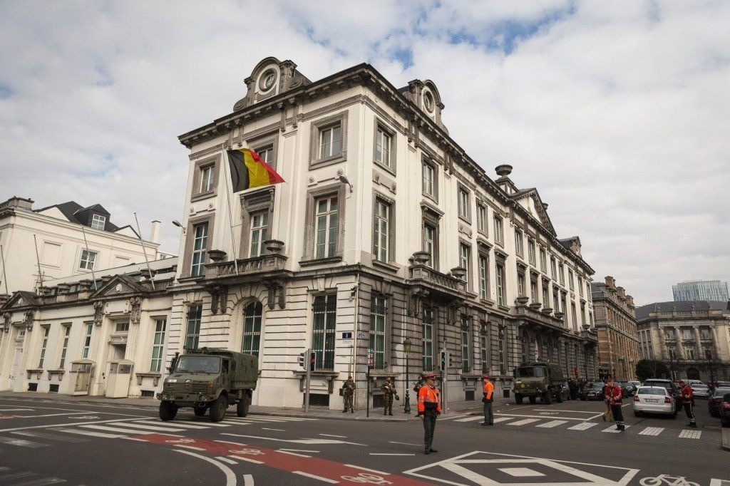 Belgian servicemen and police officers block the road outside the Prime Minister's office where a meeting of the National Security Council is held, in Brussels, on March 22, 2016, after a string of explosions rocked Brussels airport and a city metro station, killing at least 21 people, as Belgium raised its terror threat to the maximum level. The blasts come days after the dramatic arrest in Brussels on March 18 of Salah Abdeslam, the prime suspect in the Paris terror attacks that killed 130 people in November, after four months on the run. / AFP / Belga / Belgium OUT (Photo credit should read /AFP/Getty Images)
