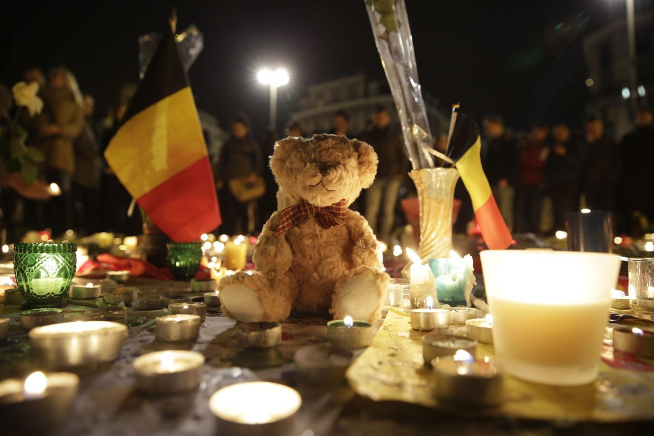 A Belgian flag, candles and a Teddy bear are pictured as people gather at a makeshift memorial on the Place de la Bourse (Beursplein) in Brussels on March 23, 2016, a day after a triple bomb attack, which responsibility was claimed by the Islamic State group, left 31 dead and hundreds injured in the Belgian capital. World leaders united in condemning the carnage in Brussels and vowed to combat terrorism, after Islamic State bombers killed 31 people in a strike at the symbolic heart of the EU. AFP PHOTO / KENZO TRIBOUILLARD / AFP / KENZO TRIBOUILLARD (Photo credit should read KENZO TRIBOUILLARD/AFP/Getty Images)