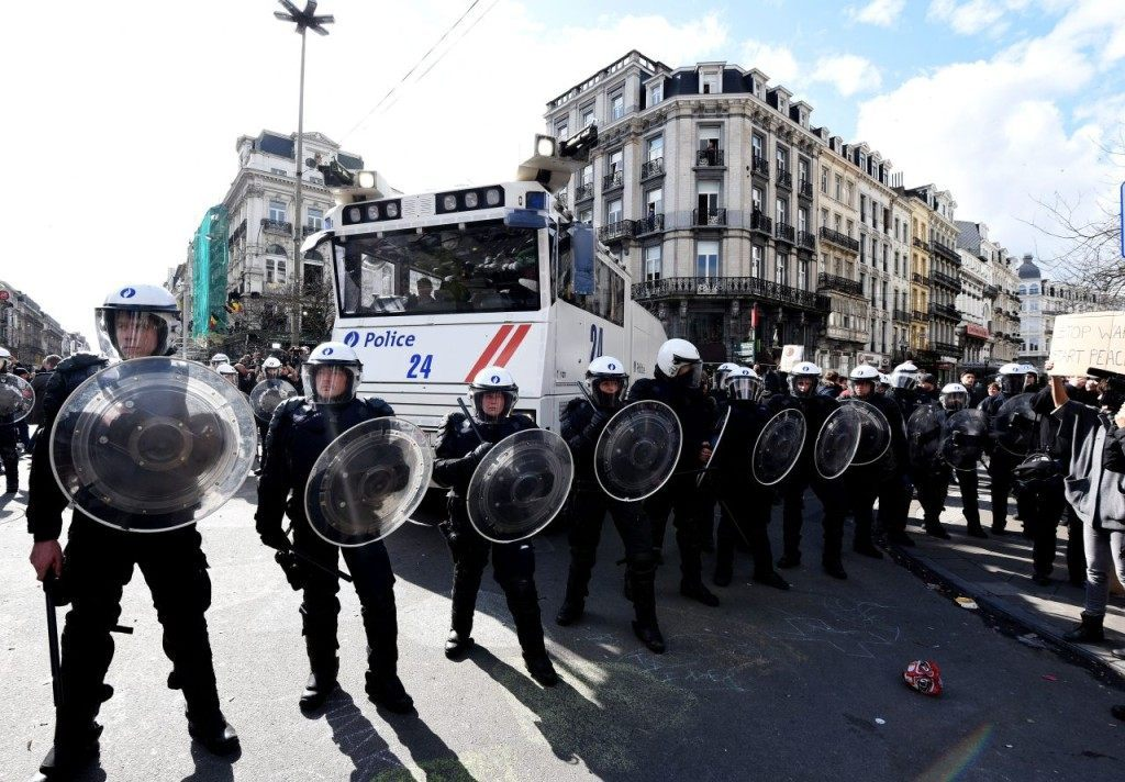 Riot police secure the area outside the stock exchange in Brussels on March 27, 2016 as tensions mounted after the square was invaded by some 200 far-right football hooligans. Police fired water a cannon at far-right football hooligans who invaded a square in the Belgian capital that has become a memorial to the victims of the Brussels attacks, an AFP journalist said. Police took action after about 200 black-clad hooligans shouting nationalist and anti-immigrant slogans moved in on the Place de la Bourse where people were gathering in a show of solidarity with the victims. / AFP / PATRIK STOLLARZ (Photo credit should read PATRIK STOLLARZ/AFP/Getty Images)
