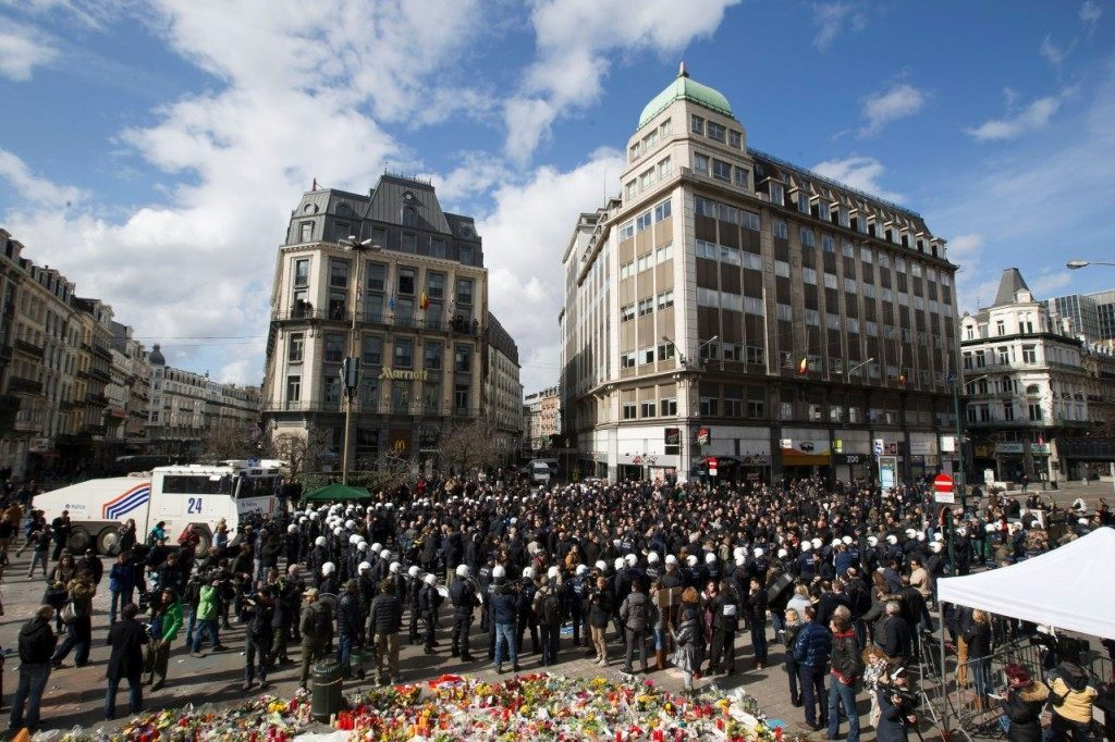 Anti-riot police officers surround far right hooligans who disturbed a tribute to the victims of terror attacks on Place de la Bourse in Brussels, on March 27, 2016. Police fired water a cannon at far-right football hooligans who invaded a square in the Belgian capital that has become a memorial to the victims of the Brussels attacks, an AFP journalist said. Police took action after about 200 black-clad hooligans shouting nationalist and anti-immigrant slogans moved in on the Place de la Bourse where people were gathering in a show of solidarity with the victims. / AFP / BELGA / KRISTOF VAN ACCOM (Photo credit should read KRISTOF VAN ACCOM/AFP/Getty Images)
