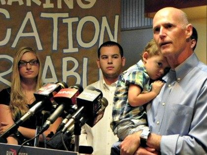Gov. Rick Scott addresses media and supporters on Monday at Beef O'Brady's in Estero, Fla.,where he discussed college affordability while holding his 2-year-old grandson, August. Scott wants to hold the line on tuition increases so more Floridians can earn degrees and enter the workforce with enhanced credentials. (AP Photo/The News-Press, …