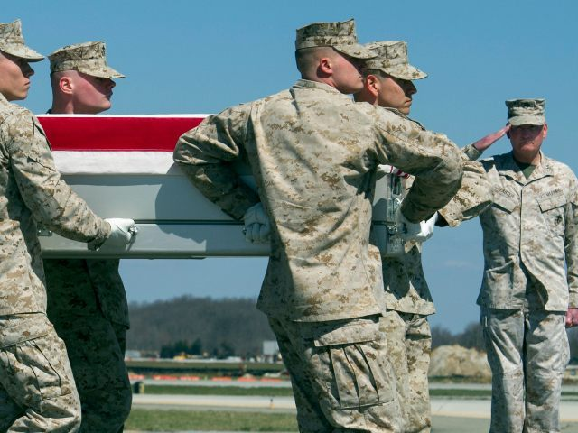 Marine Corps Lt. Gen. James Laster, director, Marine Corps Staff salutes at right as a Marine Corps carry team moves a transfer case containing the remains of Marine Corp Staff Sgt. Louis Cardin, of Temecula, Calif., Monday, March 21, 2016, at Dover Air Force Base, Del.. According to the Defense …