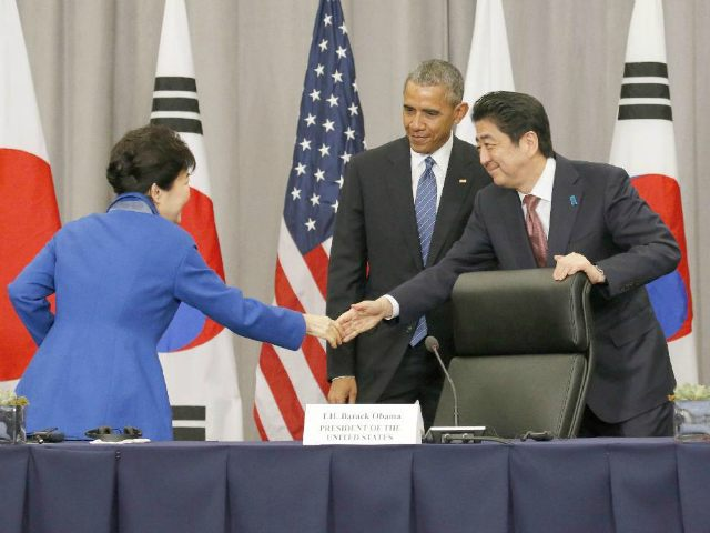 U.S. President Barack Obama (C) watches Japanese Prime Minister Shinzo Abe (R) shake hands with South Korean President Park Geun Hye following trilateral talks in Washington on March 31, 2016. The three agreed to a unified response to North Korea's nuclear test and rocket launch, as well as to future provocations by Pyongyang. (Kyodo via AP Images)