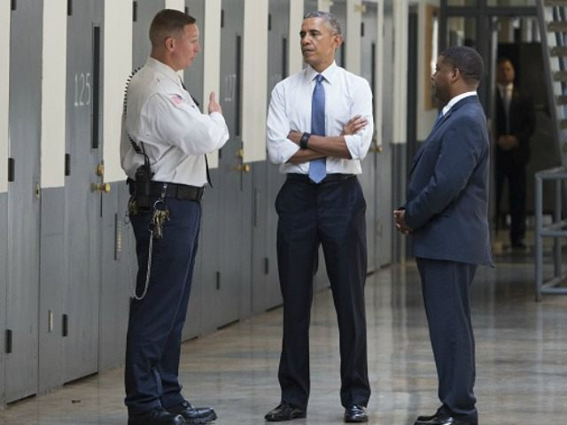 Barack Obama, alongside Charles Samuels (R), Bureau of Prisons Director, and Ronald Warlick (L), a correctional officer, tours a cell block at the El Reno Federal Correctional Institution in El Reno, Oklahoma, July 16, 2015.