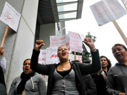 Demonstrator Catalina Lezama, center, holds up her arms during an rally against the Secure Communities program in front the state building, left, and the Federal Building, right, in San Francisco, Thursday, July 29, 2010. Some San Francisco elected officials are standing alongside immigrant advocates to protest a federal program that …