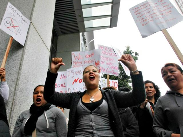 Demonstrator Catalina Lezama, center, holds up her arms during an rally against the Secure Communities program in front the state building, left, and the Federal Building, right, in San Francisco, Thursday, July 29, 2010. Some San Francisco elected officials are standing alongside immigrant advocates to protest a federal program that checks the fingerprints of anyone who's arrested against federal immigration databases.(AP Photo/Paul Sakuma)