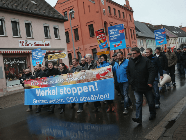 RAGUHN, GERMANY - MARCH 06: Supporters of the Alternative fuer Deutschland political party (AfD), including AfD head in Thuringia Bjoern Hoecke (C-L, wearing black), march with a banner that reads: 'Stop Merkel! Secure borders, drop the CDU!' in reference to German Chancellor Angela Merkel and the German Christian Democrats (CDU), …