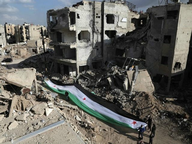 Residents and activists hold a giant a pre-Baath Syrian flag, now used by the Syrian opposition, during an anti-regime protest in the rubble of destroyed buildings in the neighbourhood of Jobar, on the eastern outskirts of the capital Damascus, on March 3, 2016. / AFP / AMER ALMOHIBANY