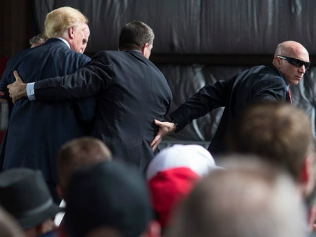 Secret Service swarms around Republican Presidential candidate Donald Trump after a bottle was thrown on stage at a Campaign Rally on March 12, 2016 in Vandailia, Ohio.