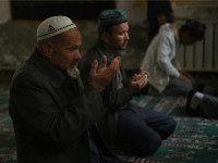 CHINA, HOTAN : This photo taken on April 16, 2015 shows Uighur men praying in a mosque in Hotan, in China's western Xinjiang region. Chinese authorities have restricted expressions of religion in Xinjiang in recent years such as wearing veils, fasting during Ramadan and young men growing beards, sparking widespread …