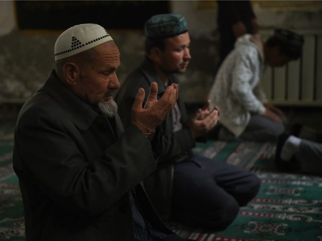 CHINA, HOTAN : This photo taken on April 16, 2015 shows Uighur men praying in a mosque in Hotan, in China's western Xinjiang region. Chinese authorities have restricted expressions of religion in Xinjiang in recent years such as wearing veils, fasting during Ramadan and young men growing beards, sparking widespread resentment. AFP PHOTO / Greg BAKER
