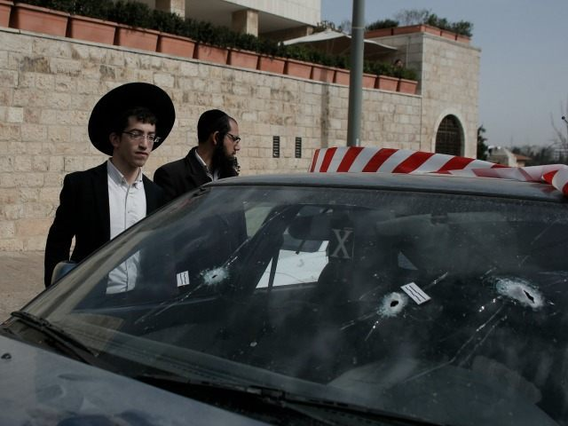 Religious Jews check a vehicle with its windshield riddled with bullet holes at the scene of an attack outside Jerusalem's Old City's New Gate on March 9, 2016. Two Palestinians opened fire at a bus in Jerusalem before fleeing and shooting again outside the Old City, leaving one person seriously …