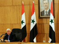 Syrian Foreign Minister Walid Muallem speaks during a press conference in front of a portrait of Syrian President Bashar al-Assad (R) on March 12, 2016 in the capital Damascus.