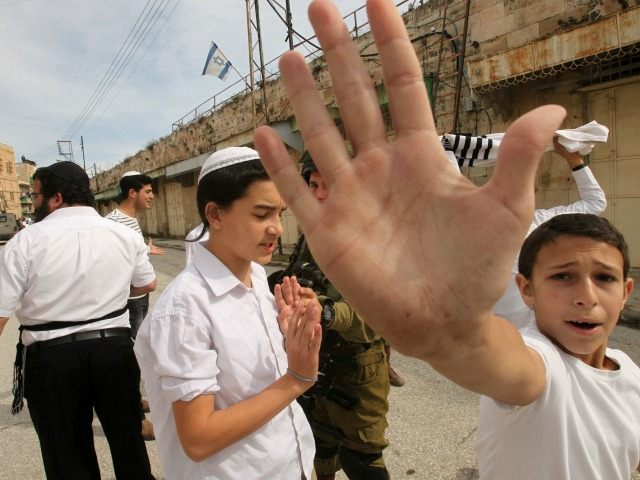 Israeli settler youth gesture to the camera in an attempt to block the view as security forces gather at the site where a Palestinian woman tried to stab an Israeli soldier before being shot dead, in the Israeli occupied West Bank city of Hebron, on February 13, 2016.