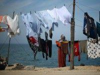 A Palestinian woman hangs her laundry next to her house at al-Shatee refugee camp in Gaza City on March 8, 2016.