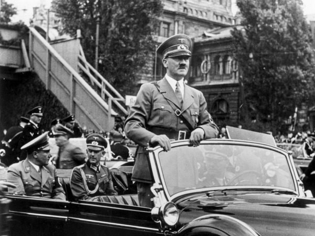 6th September 1938: The Chancellor of Germany, Adolf Hitler (1889 -1945) standing in his car as he travels through the ancient town of Nuremberg to open the Nazi Congress. In the rear seat of the car on the left is Hitler's secretary and friend Martin Bormann (1900 - 1945).
