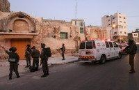 Israeli security forces gather at the site of a stabbing attack in the West Bank town of Hebron