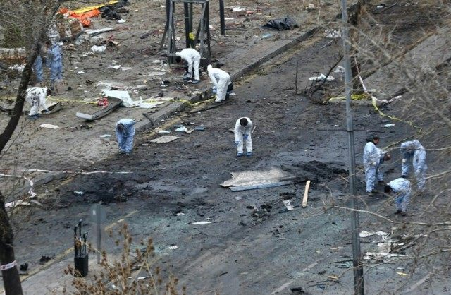 Forensic experts investigate the scene of an explosion on March 14, 2016, the day after a suicide car bomb ripped through a busy square in central Ankara killing at least 34 people and wounding 125, officials said