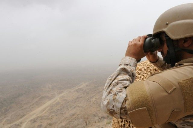 A Saudi soldier looks through binoculars from a position in the al-Dokhan mountains, on the Saudi-Yemeni border in southwestern Saudi Arabia, on April 13, 2015