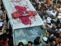 Pakistani supporters of convicted murderer Mumtaz Qadri gather around a vehicle carrying his body during his funeral in Rawalpindi on March 1, 2016