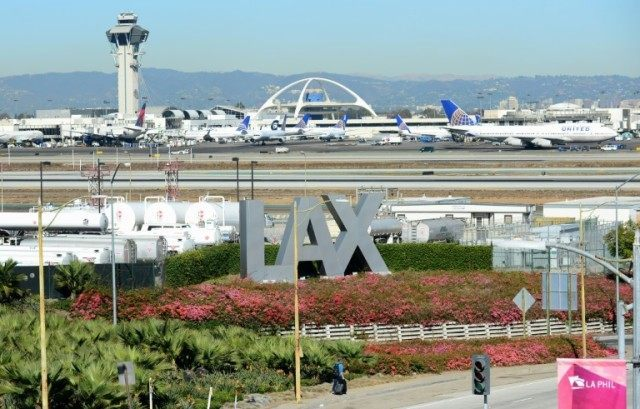 A traveller pulls his bags while walking past an LAX sign at Los Angeles International Airport on November 1, 2013 in Los Angeles, California