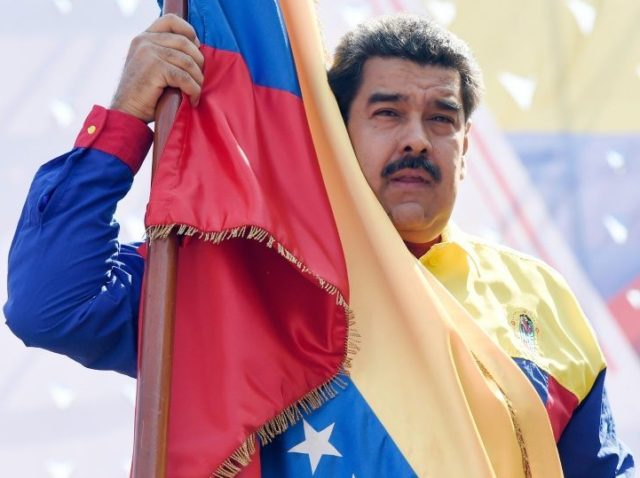 Venezuelan President Nicolas Maduro holds a flag during a demonstration against the United States' decision to renew sanctions on several top Venezuelan officials, in Caracas on March 12, 2016