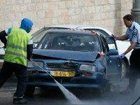 An Israeli policeman inspects a vehicle with its windshield riddled with bullet holes at the scene of an attack outside Jerusalem's Old City's New Gate on March 9, 2016. Two Palestinians opened fire at a bus in Jerusalem before fleeing and shooting again outside the Old City, leaving one person …