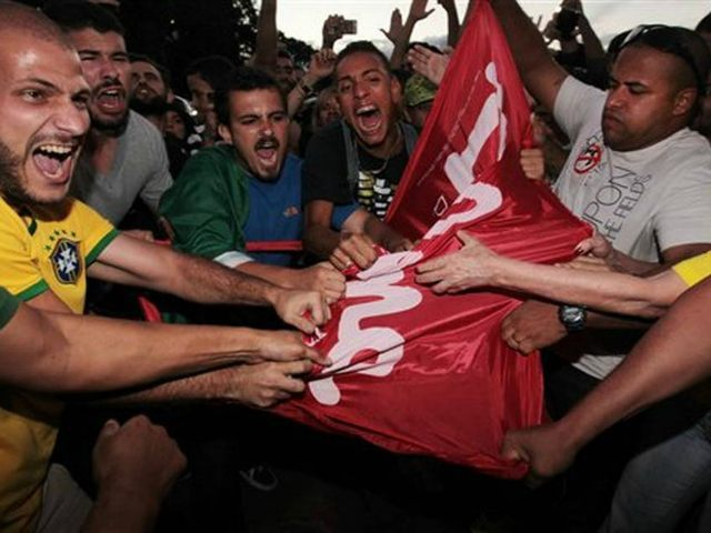 Anti-government protestors try to rip apart a Workers' Party flag during a demonstration outside Planalto presidential palace as they demand the impeachment of Brazil's President Dilma Rousseff in Brasilia, Brazil, Thursday, March 17, 2016. Rousseff's critics accuse her of a transparent maneuver aimed at helping her mentor, the once wildly …