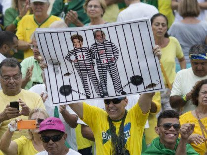 FILE - In this March 13, 2016 file photo, a demonstrator holds a poster with the photo of Brazilian president Dilma Rousseff and former President Luiz Inacio Lula da Silva in prison stripes during a protest on Copacabana beach in Rio de Janeiro, Brazil. It was the best of times …