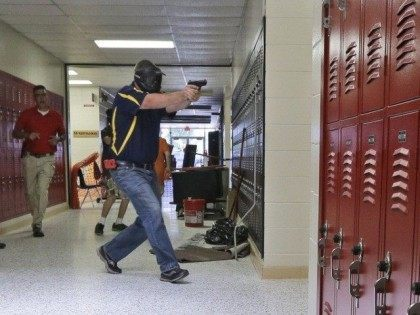 In this photo taken July 11, 2013, a Clarksville schools faculty member, wearing a protective mask, rear center, carries a practice handgun toward a classroom in the city's high school in Clarksville, Ark., as students portray victims in a mock school shooting scenario. Twenty Clarksville School District staff members are …