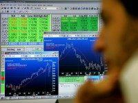 Market displays on a monitor show the latest international currency rates, in green, and fluctuations in the Israeli stock market, as a broker keeps an eye on the news of Israeli Prime Minister Ariel Sharon's slightly improved health in the trading room of the First International Bank of Israel January …