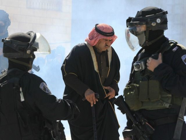 A Palestinian man reacts upon inhaling tear gas fired by Israeli security forces during a protest near the Jewish settlement of Kiryat Arba demanding the reopening of Shuhada Street in the Israeli occupied West Bank city of Hebron and to commemorate the Ibrahimi Mosque massacre of 1994, on February 26, …