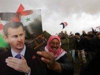 Syrian volunteers and their relatives wave the national flag and portraits of President Bashar al-Assad as they celebrate at the end of a paramilitary training conducted by the Syrian army in al-Qtaifeh, 50 kms north of the capital Damascus on February 22, 2016.