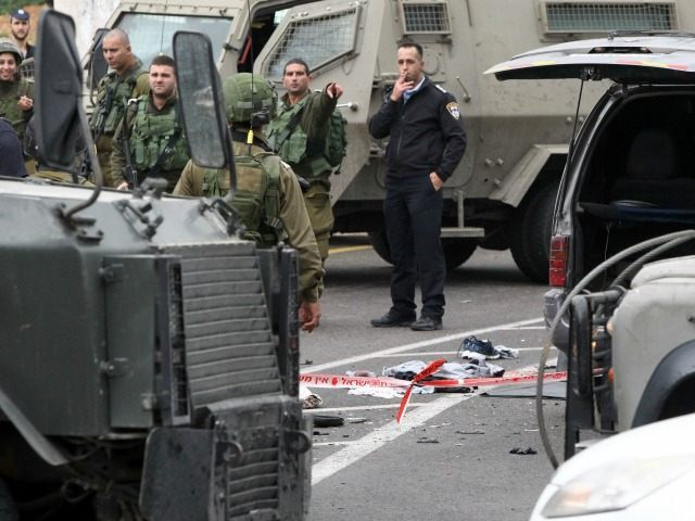 Israeli security forces stand guard at the scene where three Palestinians carried out two attacks -- a shooting and a car ramming -- on Israelis at the entrance of the Israeli settlement of Kiryat Arba in the southern occupied West Bank before they were shot dead on March 14, 2016.