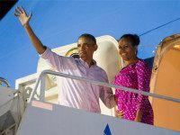 President Barack Obama, left, and first lady Michelle Obama wave as they board Air Force One to depart from Joint Base Pearl Harbor-Hickam at the end of their family vacation, on Saturday, Jan. 2, 2016, in Honolulu, Hawaii. (AP Photo/Evan Vucci)