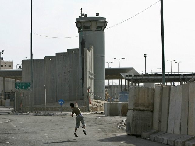 A Palestinian boy throws stones towards an Israeli army watchtower during clashes between Palestinian stone-throwers and Israeli soldiers at the Qalandia checkpoint near the West Bank city of Ramallah on October 16, 2009. Israel slammed the adoption of an 'unjust' UN report on the Gaza war on October 16, warning …