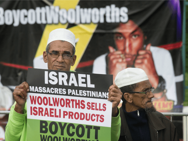 A Muslim man holds a placard reading 'Israel massacres Palestinians. Woolworths sells Israeli products', during a protest against Grammy-winning American musician Pharrell Williams near the Grand west Casino where he was holding a concert in Cape Town, on 21 September, 2015.