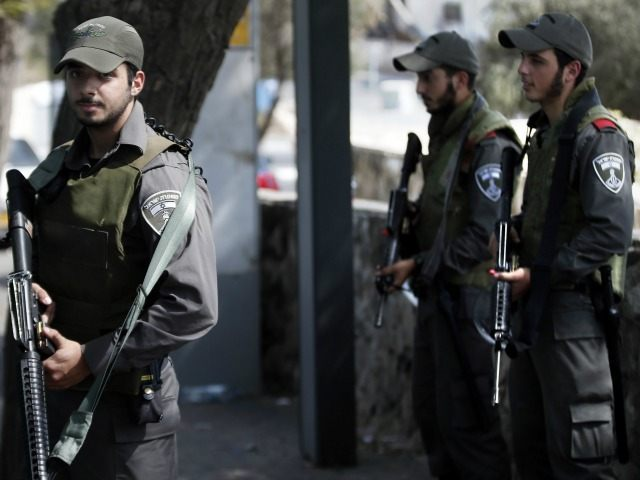 Israeli border policemen stand guard at a bus stop in the east Jerusalem Jewish settlement of Armon Hanatsiv, adjacent to the Palestinian neighbourhood of Jabal Mukaber, on October 18 2015.