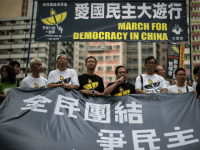 Pro-democracy protesters take turns to speak as they stand behind a huge banner in Hong Kong on May 31, 2015, before a rally to commemorate the 1989 crackdown at Tiananmen Square in Beijing, prior to the incident's 26th anniversary on June 4.