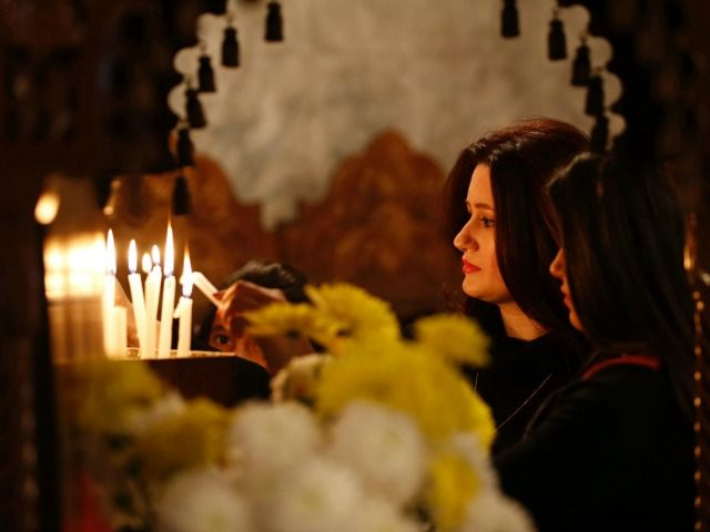 A Palestinian Christian woman lights a votive candle during Orthodox Christmas celebrations at the Saint Porphyrios Greek Orthodox church in Gaza City on January 7, 2016.