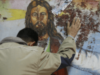 An Egyptian Christian mourns as he stands next to a blood-stained painting of Jesus Christ on January 2, 2011 outside the Al-Qiddissine (The Saints) church in Alexandria, following a New Year's Eve car bomb attack on the Coptic church in the northern Egyptian city in which 21 people were killed.