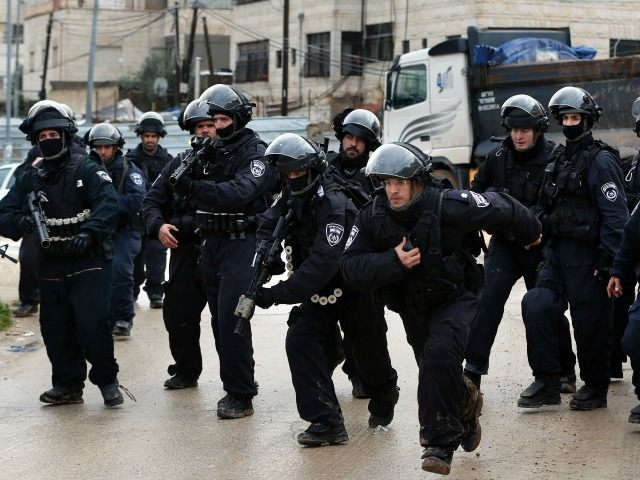 Israeli policemen secure an area where a house belonging to a Palestinian family is demolished by Israeli authorities that they said was built without a municipality permit, in the Arab east Jerusalem neighbourhood of Shuafat on January 27, 2016.