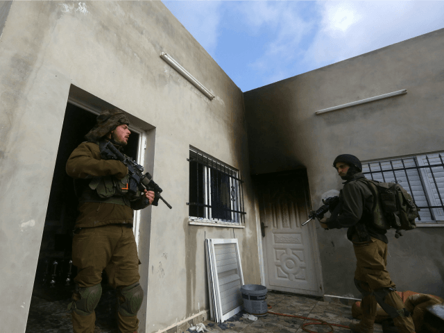 Israeli security forces stand guard outside a Palestinian burnt-out house belonging to a key witness to an arson attack which took place last year by Jewish extremists that killed a Palestinian family, in the Israeli occupied West Bank village of Duma, after fire broke out in the home on March …