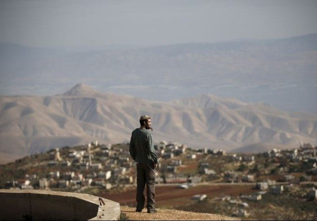 Jewish settler Refael Morris stands at an observation point overlooking the West Bank village of Duma, near Yishuv Hadaat, an unauthorized Jewish settler outpost.