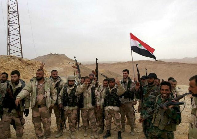 Forces loyal to Syria's President Bashar al-Assad flash victory signs and carry a Syrian national flag on the edge of the historic city of Palmyra in Homs Governorate, in this handout picture provided by SANA on March 26, 2016. REUTERS/SANA/HANDOUT VIA REUTERS