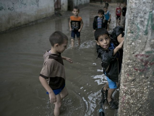 Palestinian boys stand on a flooded street after heavy rain in Khan Yunis in the southern Gaza Strip on October 7, 2015.