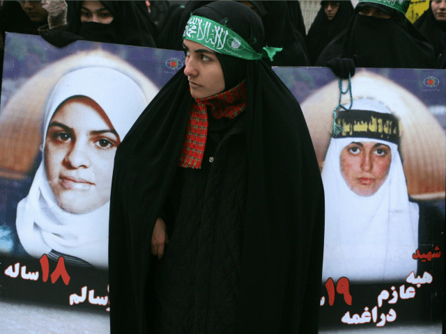 An Iranian woman stands between portraits of Palestinian female suicide bombers during a protest against Israel's blockade of the Gaza Strip, in front of the United Nation's office in Tehran, 24 January 2008.