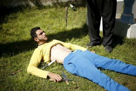 Palestinian Mohammad Baraka has knives dropped on his stomach as he exercises in Deir al-Balah in the central Gaza Strip