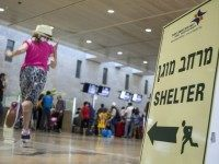 A girl runs past a sign directing passengers to a shelter at Ben Gurion International airport, near the Mediterranean Israeli coastal city of Tel Aviv on August 21, 2014, following a warning issued by Hamas's armed wing that they will target the airport from 6 am (0300 GMT) in a …