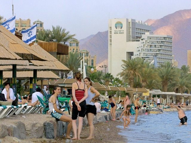 Even as evening draws near, tourists enjoy one of the many beaches in the southern Israeli city of Eilat May 4, 2001, beaches which in previous years were packed full with visitors taking advantage of the almost year-round sun and warm weather.